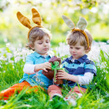 Two little kids playing with Easter chocolate bunny outdoors Stock Image