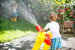 Two little kids playing with garden hose in summer. Adorable little kid boy and his brother playing and splashing together with a garden hose on hot and sunny royalty free stock photos