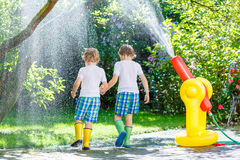 Two little kids playing with garden hose in summer. Two adorable little kid boys playing together with a garden hose on hot and sunny summer day. Two siblings stock photo