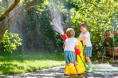 Two little kids playing with garden hose in summer Royalty Free Stock Photo
