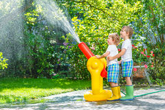 Two little kids playing with garden hose and water Royalty Free Stock Photos