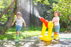 Two little kids playing with garden hose and water in summer Royalty Free Stock Photography