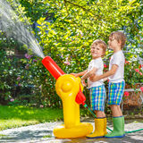 Two little kids playing with garden hose and water in summer Royalty Free Stock Images