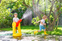 Two little kids playing with garden hose and water in summer. Two funny little friends playing together and splashing with a garden hose on hot and sunny summer royalty free stock photo