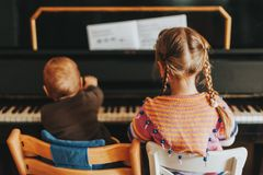 Two little kids playing on piano. Toddler girl and baby boy practicing music at home, back view Royalty Free Stock Photos