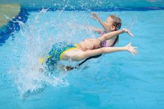 Two little kids playing in the pool Stock Images