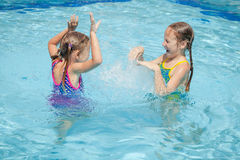 Two little kids playing in the pool Stock Photo
