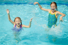 Two little kids playing in the pool Stock Image