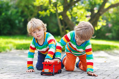 Two little kids playing with red school bus Stock Photos