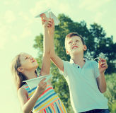 Two little kids playing with simple paper planes. On sunny day Royalty Free Stock Image