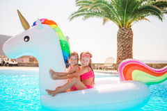 Two little kids playing in the swimming pool. Little happy adorable girl in outdoor swimming pool Stock Images