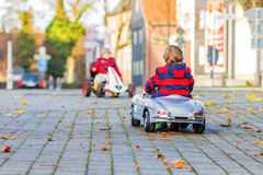 Two little kids in red jackets driving old vintage and race cars Stock Photography