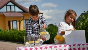 Two little kids are selling lemonade at a homemade lemonade stand on a sunny day with a price sign for an entrepreneur