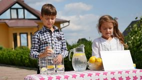 Two little kids are selling lemonade at a homemade lemonade stand on a sunny day with a price sign for an entrepreneur Royalty Free Stock Image