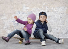 Kids on a skateboard. Two little kids sitting on skateboard in front of brick wall royalty free stock photo
