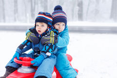 Two little kids  sitting together on sledge on cold day Royalty Free Stock Images