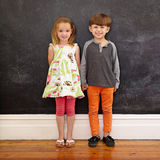 Two little kids standing together against blackboard Stock Photography