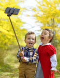 Two little kids taking selfie in park in autumn Royalty Free Stock Image