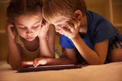 Two little kids watching cartoons. Portrait of a two cute little kids lying down on the floor and watching animated cartoons on the tablet, brother and sister Royalty Free Stock Photography