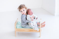 Two little kids in a wood toy bed Stock Image