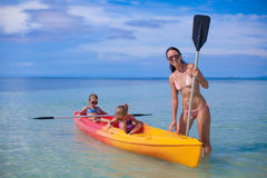 Two little kids and young mom kayaking at tropical Stock Image