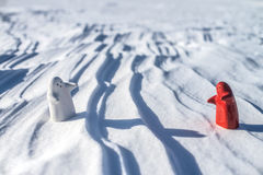 Two little lonely white and red people stay on snow Royalty Free Stock Images