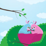 Two little lovebirds in their nest. Two cute little pink and blue cartoon lovebirds in their nest sitting close together sharing a fat juicy worm Stock Photography
