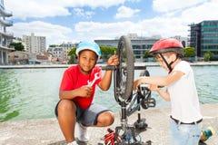 Two little mechanics repairing bike outdoors Stock Photo