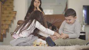 Two little Middle Eastern children fighting for the toy at the foreground and their mother holding her head desperately. At the background. Siblings playing stock video footage