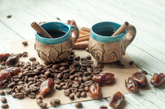Two little old pottery handmade cups of coffee, coffee beans, sweet dried dates and cinnamon sticks Royalty Free Stock Photography