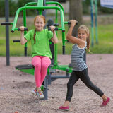 Two little peppy girls is engaged in fitness equipment outdoor. Stock Photography