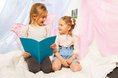 Two little pixies with wings reading bedtime story Stock Photos
