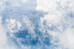 Two Little Planes. Two small aircraft in a blue cloudy sky Stock Photos