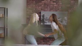 Two little girls with blond and dark hair jumping holding hands in the living room. Brunette girl and albino girl with stock footage