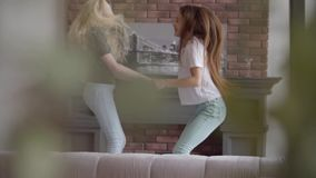 Two little girls with blond and dark hair jumping holding hands in the living room. Brunette girl and albino girl with stock video footage