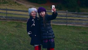 Two little pretty girls make selfie on cell phone outdoors stock video