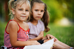 Two little pretty girls reading Stock Images