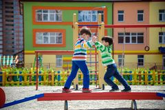 Free Two Little School And Preschool Kids Boys Playing On Playground Outdoors Together. Children Having Competition Standing On Log Stock Image - 151363661