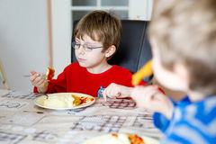 Two little school boys eating potato mash and chicken breast indoor. Blond children in domestic kitchen or in school canteen Cute kids and healthy food Stock Images
