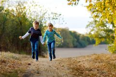 Two little school kids boys running and jumping in forest. Happy children, best friends and siblings having fun on warm. Sunny day early autumn. Twins and royalty free stock photography