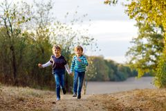 Two little school kids boys running and jumping in forest. Happy children, best friends and siblings having fun on warm. Sunny day early autumn. Twins and stock images