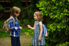 Two little school students, the boy and the girl, cheerfully communicate on the schoolyard. Stock Photo