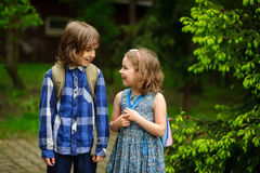 Two little school students cheerfully communicate on the schoolyard. Stock Images