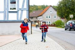 Two little schoolkids boys running and driving on scooter on autumn day Stock Images