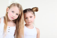 Two little serious girl in white clothes look at camera Royalty Free Stock Photography