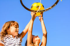 Two little seven year old girls aplaying basketball outdoors. Two little seven year old girls are playing basketball outdoors royalty free stock photography