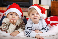 Two little sibling boys being happy about christmas present. Portrait of two little sibling boys in santa hats, indoor with christmas decoration Royalty Free Stock Photo