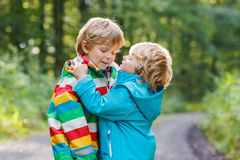 Two little sibling boys in colorful raincoats and boots walking Royalty Free Stock Images