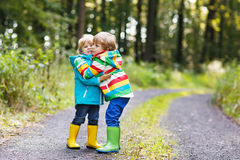 Two little sibling boys in colorful raincoats and boots walking Stock Photos