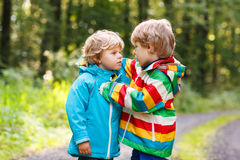 Two little sibling boys in colorful raincoats and boots walking Royalty Free Stock Image